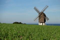 Mulino a vento vicino alla costa con la vista al mare immagini stock