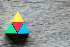 Mulit color toy block compound as triangle shape. On wood background Royalty Free Stock Image