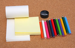 Muliticolored pencils and notepads. Muliticolored pencils and notepad on brown Stock Photos