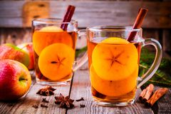 Mulled apple cider with cinnamon and anis in glass mugs. On rustic wooden table stock photo