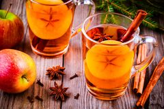 Mulled apple cider with cinnamon and anis in glass mugs. On rustic wooden table stock photography