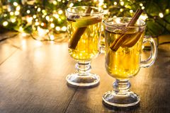 Mulled cider in glass, ornaments and christmas light on wood stock images