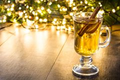 Mulled cider in glass, ornaments and christmas light on wood. En table. Copyspace Stock Photos