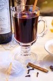 Mulled red wine in a glass mug. A glass mug filled with hot mulled red wine, orange peels and spices (Gluhwein) on a white table-cloth Stock Images