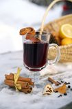 Mulled red wine in a glass mug outdoor in winter. A glass mug filled with hot mulled red wine, orange peels and spices (Gluhwein) on a snowy table Stock Photo
