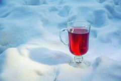 Mulled red wine glass standing on snow. Mulled red wine glass wuth orange inside standing on snow royalty free stock photos