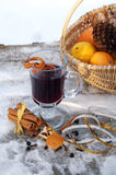 Mulled red wine on a snowy table outdoor in winter. A glass mug filled with hot mulled red wine, orange peels and spices (Gluhwein) on a snowy table Stock Photography