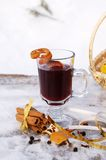Mulled red wine on a snowy table outdoor in winter. A glass mug filled with hot mulled red wine, orange peels and spices (Gluhwein) on a snowy table, vertical Royalty Free Stock Photography