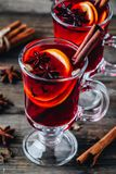 Mulled red wine with spices and orange in glass on a wooden rustic background stock photos