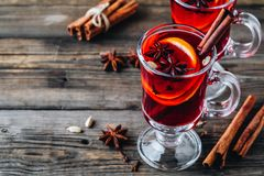 Mulled red wine with spices and orange in glass on a wooden rustic background stock photo