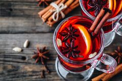 Mulled red wine with spices and orange in glass on a wooden rustic background royalty free stock photo