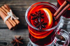 Mulled red wine with spices and orange in glass on a wooden rustic background royalty free stock photos