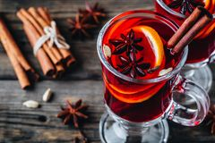 Mulled red wine with spices and orange in glass on a wooden rustic background stock images