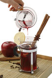 Mulled wine. Glass of mulled wine being poured from jug with spices on wooden tray stock photo