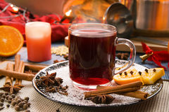 Mulled wine. A glass cup of hot red mulled wine on a plate with a saucepan in the background an Christmas decoration Stock Photography