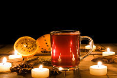 Mulled wine. Lit by candle light, decorated with spices, oranges and candles, isolated on a black background Royalty Free Stock Image