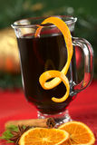 Mulled Wine. Hot spiced mulled wine garnished with orange peel (Selective Focus, Focus on the front rim of the glass and the orange peel at the rim Stock Photos