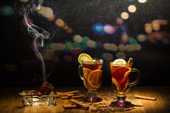 Mulled wine against the background. Mulled wine on an evening background with cinnamon, cigar and lemon Stock Photo