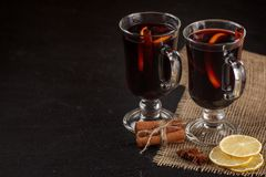 Mulled wine banner. Glasses with hot red wine and spices on dark background. Modern dark mood style. Royalty Free Stock Images