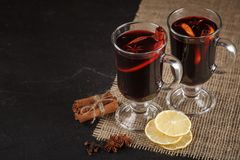 Mulled wine banner. Glasses with hot red wine and spices on dark background. Modern dark mood style. Royalty Free Stock Image