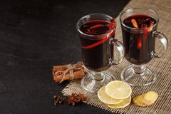 Mulled wine banner. Glasses with hot red wine and spices on dark background. Modern dark mood style. Stock Images