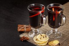 Mulled wine banner. Glasses with hot red wine and spices on dark background. Modern dark mood style. Stock Photography