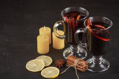 Mulled wine banner. Glasses with hot red wine and spices on dark background. Modern dark mood style. Stock Photos