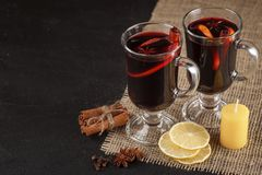 Mulled wine banner. Glasses with hot red wine and spices on dark background. Modern dark mood style. Royalty Free Stock Photos