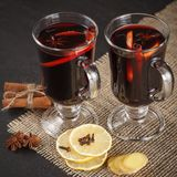 Mulled wine banner. Glasses with hot red wine and spices on dark background. Modern dark mood style. Stock Image