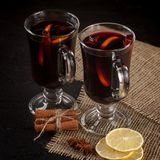 Mulled wine banner. Glasses with hot red wine and spices on dark background. Modern dark mood style. Stock Photo