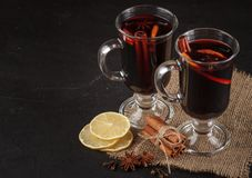 Mulled wine banner. Glasses with hot red wine and spices on dark background. Modern dark mood style. Royalty Free Stock Photo