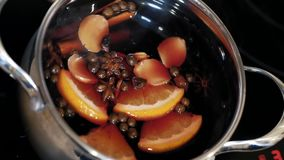 Mulled wine is being mixed in a pot. Cooking traditional drink for Christmas. Mulled wine preparations. Close up stock video footage