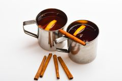 Mulled wine or beverage with cinnamon. Mugs with mulled wine or hot drink and cinnamon aroma sticks, white background Royalty Free Stock Images