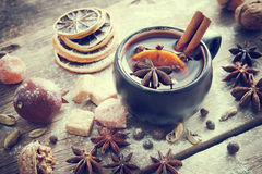 Mulled wine in black mug and ingredients on table. Retro toned Stock Photography