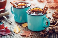 Mulled wine in blue enameled mugs with spices and citrus fruit on table with autumn leaves. Royalty Free Stock Photography