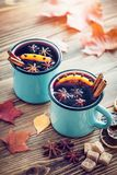 Mulled wine in blue enameled mugs with spices and citrus. Stock Photo