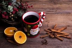 Mulled wine with christmas decorations shot on a wooden background angled. Mulled wine with orange and cloves and cinnamon and christmas decorations shot from Stock Photography