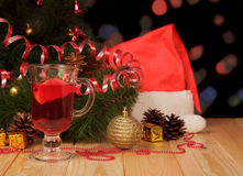 Mulled wine, Christmas tree, gifts and hat on abstract dark. Stock Photos