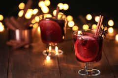 Mulled wine with cinnamon, anise and orange in glass on table stock photos
