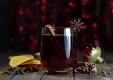 Mulled wine with cinnamon, an anisetree, a carnation and a New Year's sphere. Against the background of fires Stock Photos