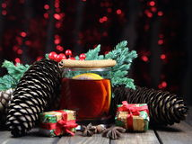 Mulled wine with cinnamon, an anisetree, cones, a juniper and gifts Royalty Free Stock Image