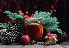 Mulled wine with cinnamon, an anisetree, cones, a juniper and gifts. Against the background of festive fires Stock Images