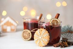 Mulled wine with cinnamon and cookie on table stock image