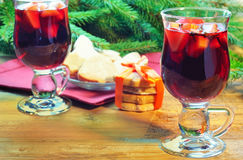 Mulled wine with cinnamon sticks and christmas bell-formed cookies Royalty Free Stock Photos