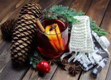 Mulled wine with cones with a jumper with deer and a knitted scarf, a lemon, a juniper, cinnamon, an anisetree and apple Royalty Free Stock Image
