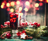 Mulled wine, cookies and holiday decorations on table with bokeh lighting Stock Image