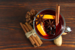 Mulled wine. Cup with mulled wine and lemon slices and cinnamon with anise on wooden background royalty free stock image