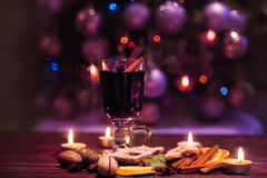 Mulled wine on a dark background. Winter Christmas Eve with candles. Mulled wine, hot drink in a high glass  on a dark background.  Soft focus. Winter Christmas Royalty Free Stock Image