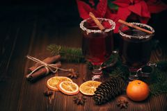 Glasses of mulled wine on wooden table. Mulled wine, fir branches, spices and christmas decoration on a wooden table. Winter holidays stock image