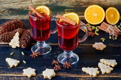Mulled wine with fresh orange slices and various winter spices on the black wooden background decorated with Christmas cookies. Side view royalty free stock photos
